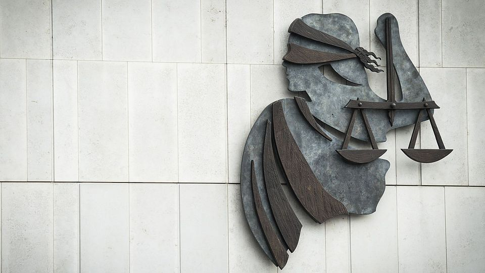 Modern wall sculpture of Lady Justice with blindfold and scales